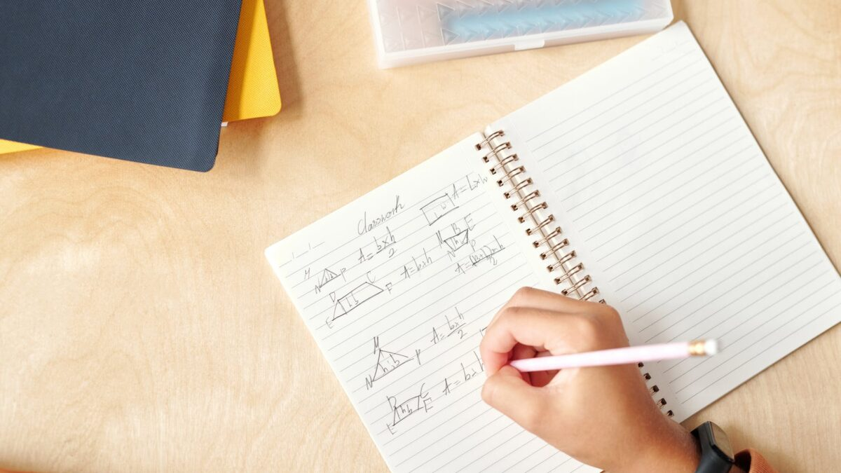 a person writing on the notebook