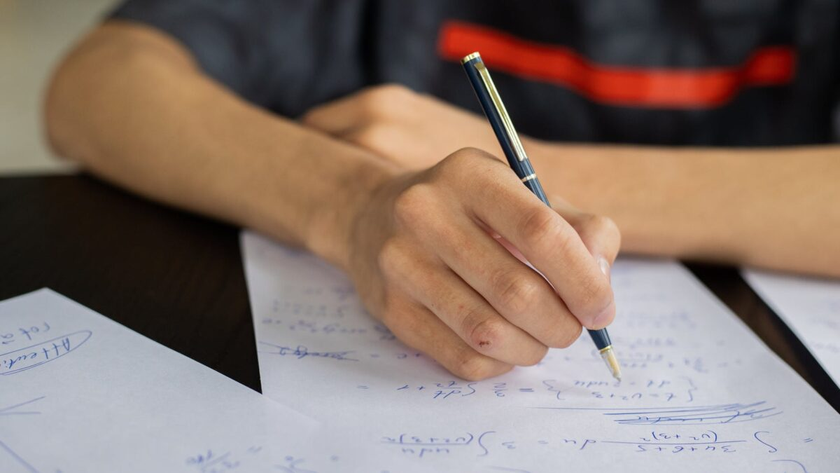 crop man writing on paper while studying